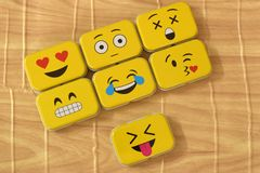 Emoji Metal Tins. Some emoji metal tins or smiley boxes, on a brown background stock photography