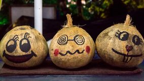 Emoji painted on coconuts sold at the Asian market. Emoji painted on coconuts sold on the counter of the Asian market royalty free stock photo