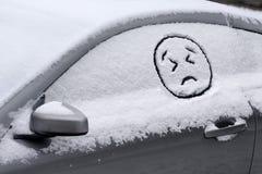 Emoji triste/enojado hace frente a exhausto en la ventanilla del coche cubierta con nieve Foto de archivo libre de regalías