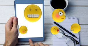 Emojis coming out from tablet PC while man using it Stock Photo