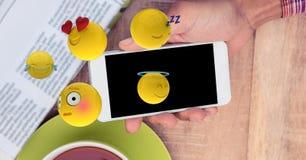 Emojis przybycie z mądrze telefonu trzymającego osobą na stole ilustracji