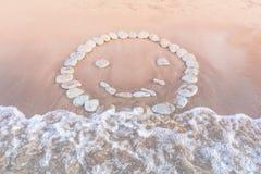 Emoticon av kiselstenar på sand arkivbild