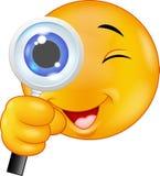 Emoticon del fumetto che tiene una lente d'ingrandimento Fotografie Stock