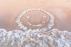 Emoticon of pebbles on sand Stock Photography