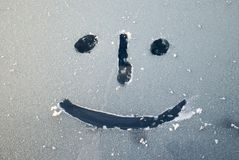 Emoticon. Smiley face drawn on a frozen glass royalty free stock photo