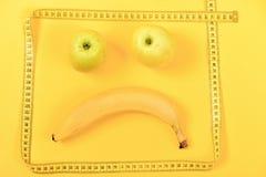 Emoticon som göras av äpplen i grön färg och banan arkivfoton