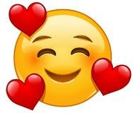 Emoticon sonriente con 3 corazones ilustración del vector