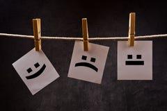 Emoticons σε χαρτί σημειώσεων που συνδέεται με το σχοινί με τις καρφίτσες ενδυμάτων Στοκ Εικόνες