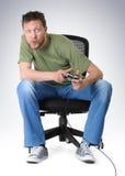 Emotie gamer om op stoel met bedieningshendel te spelen Stock Foto's