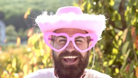 Emotiemens met grappige hipster roze zonnebril en grappige roze hoed Gebaarde gekke mens die de camera bekijken Maak grappig stock footage