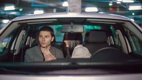 Emoties van een jong paar in de auto in het ondergrondse parkeren stock footage