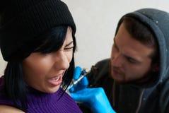 Emoties van een meisje terwijl het maken van een tatoegering Stock Afbeelding