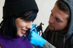 Emoties van een meisje terwijl het maken van een tatoegering Stock Foto