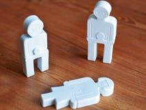 Emoties van spijt tussen mensen, het concept sociale steun, weinig stuk speelgoed mensen op een houten achtergrond stock afbeeldingen