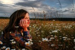 Emotion. Portrait of the girl in a field with camomile and dramatic sky stock photos