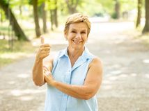 Portrait of a happy mature woman in the park. Emotion, age and people concept - portrait of happy senior woman laughing in the park. Thumb up Stock Images