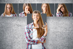 Emotion concept. Young european female hiding herself behind poster with smiling face. Row of faces with different expressions in the background. Emotion concept Royalty Free Stock Image
