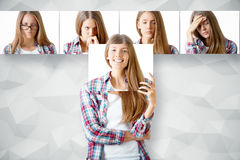 Emotion concept. Young european woman hiding herself behind poster with smiling face. Row of faces with different expressions in the background. Emotion concept Royalty Free Stock Image