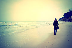Emotion conceptual image. Lonely woman walking on the beach. Instagram vintage picture Stock Image
