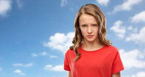 Sad or angry teenage girl in red t-shirt over sky. Emotion, expression and people concept - sad or angry teenage girl in red t-shirt over blue sky and clouds stock photography
