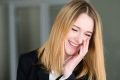 Emotion face happy smiling cheerful pleased woman. Emotion face. happy smiling cheerful pleased woman. business lady at office workspace. young beautiful blond Royalty Free Stock Photography
