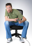 Emotion gamer to play on chair with joystick Stock Photos