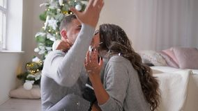 Emotion of happiness, artificial snow falls on two lovers sitting on floor in the room near New Year tree. Emotion of happiness, artificial snow falls on two stock footage