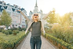 Emotion joy and happiness, young happy woman raised her hands up, outdoor background, golden hour.  royalty free stock image