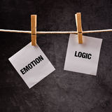 Emotion or Logic concept. Words printed on note paper and attached to rope with clothes pins Royalty Free Stock Photos
