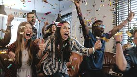 Emotion. Multi-ethnic fans celebrate winning. Confetti 4K slow motion. Passionate supporters shout watching game on TV. Emotion. Multi-ethnic fans celebrate stock images