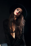 Emotion sexy female model posing in black shirt and elegant hat Royalty Free Stock Photography
