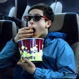 Guy teen in 3d glasses sits in a cinema chair and eats popcorn. The emotion of surprise on the boy`s face while watching an royalty free stock photography