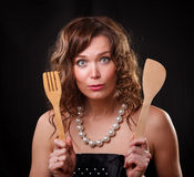 Emotion surprised beautiful woman with kitchen goods. On a dark wall Royalty Free Stock Photos