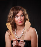 Emotion surprised beautiful woman with kitchen goods. On a dark wall stock images