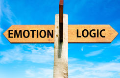 Emotion versus Logic. Wooden signpost with two opposite arrows over clear blue sky, Emotion versus Logic messages Royalty Free Stock Photos