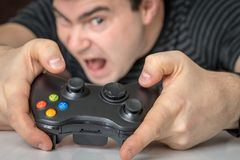 Emotional addicted man playing video games stock image