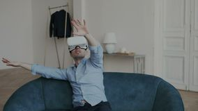 Emotional adult man is watching 360 degree video at home, wearing VR headset. He is very surprised, looks around and stock footage