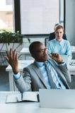 emotional african american businessman in eyeglasses using headset royalty free stock images