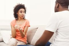 Emotional black couple drinking coffee on sofa at home. Emotional african-american couple having rest at cozy home and chatting. Family leisure, lazy weekend and Stock Image