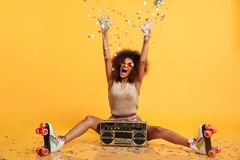 Emotional african disko woman in retro wear and roller scates th Royalty Free Stock Photo
