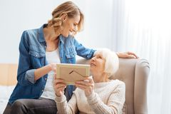 Emotional aged woman showing photos while being with her granddaughter. Sharing memories. Kind calm senior women feeling glad while looking at her attentive Stock Photography