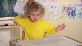 Emotional angry baby tearing painting paper in her room