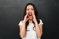 Emotional asian woman in casual t-shirt screaming or calling wit Stock Image