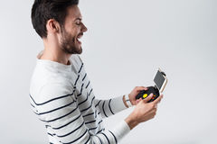 Emotional bearded man using portable gamepad. Royalty Free Stock Photo