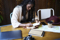 Emotional beautiful afro american woman. Experienced female traveller wear trendy outfit sitting in coffee shop and recording impressions of new city in notebook Royalty Free Stock Photos