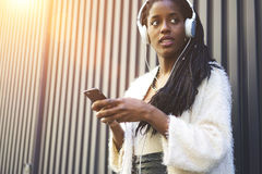 Emotional beautiful afro american woman modern and high-quality earphones Stock Images