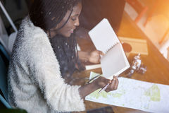 Emotional beautiful afro american woman for new journey during good day. Cropped image of smiling afro american hipster girl reading notebook with mock up space Royalty Free Stock Photo