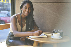 Emotional beautiful afro american woman. Portrait of afro american correspondent working on research cool cafe places for media sitting indoors and looking at Stock Photo
