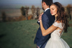 Emotional beautiful bride hugging newlywed groom from behind at stock photography