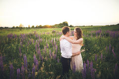 Emotional beautiful bride hugging newlywed groom from behind sunset at a field closeup Royalty Free Stock Image